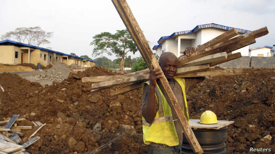 FILE - A construction worker carries timber at a housing project being built in an old cocoa-producing community just outside Equatorial Guinea's capital Malabo February 5, 2014. On land cleared of tropical forest, gleaming new office towers, apartme
