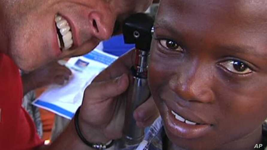 Frederic Rondeau of Starkey Hearing Foundation outfits a hearing aid for a Haitian child, Marchand Dessalines, Haiti, January 9, 2012.