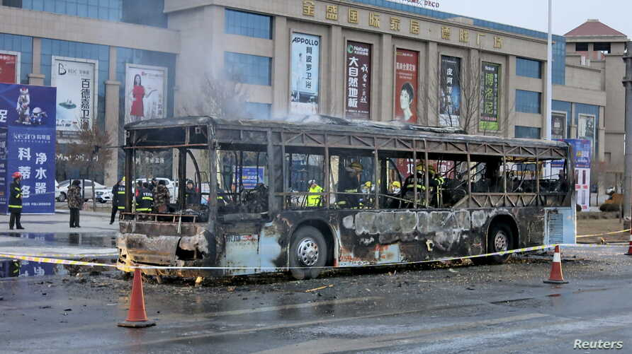 Firefighters are seen working inside a burnt bus after a fire on a street in Yinchuan, Ningxia Hui Autonomous Region, China, Jan. 5, 2016.