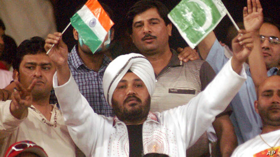 FILE - Indian pop star Daler Mehndi, center, waves Indian and Pakistani flags while watching a cricket match in Lahore, Pakistan, March 24, 2004.