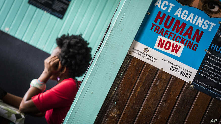 FILE - A prostitute is shown being questioned during a raid in night clubs in Georgetown, Guyana, April 7, 2018. A 13-country police operation freed nearly 350 people from human trafficking networks and arrested 22 people across the Caribbean and Sou