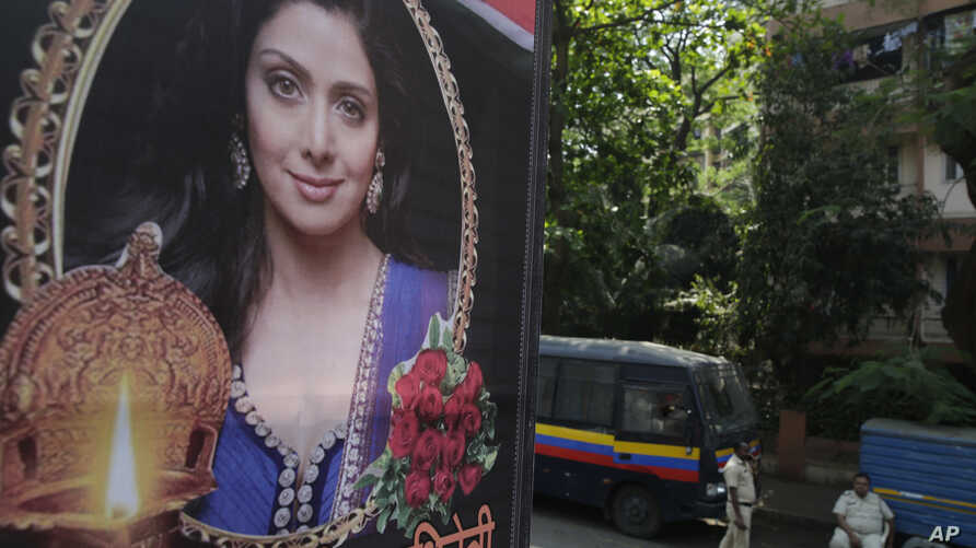 Indian policemen guard near a picture of Indian actress Sridevi displayed outside her residence in Mumbai, India, Feb. 27, 2018.