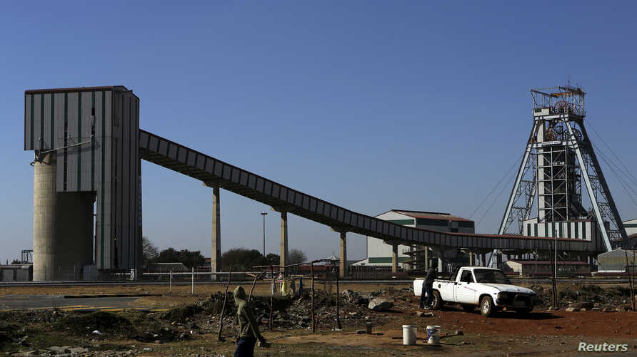 FILE - A man walks past the Doornkop Gold Mine, about 19 miles west of Johannesburg.