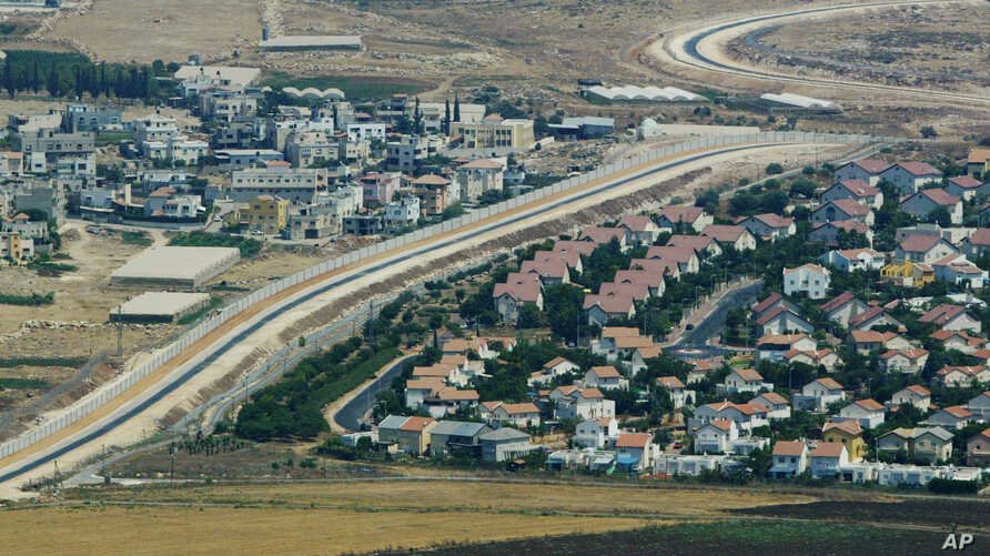 FILE - An aerial view over West Bank showing a Palestinian village, left, and a Jewish settlement, right, separated by a wall, part of the separation fence Israel is building.