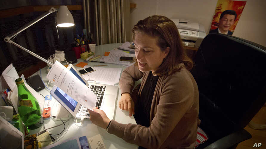 French journalist Ursula Gauthier, a reporter for the French news magazine L'Obs, holds a statement criticizing her from the Chinese Ministry of Foreign Affairs as she sits at her desk in her apartment in Beijing, Dec. 26, 2015.