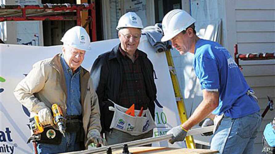 Former President Jimmy Carter, left, former Vice-President Walter Mondale, center, and Minneapolis Mayor R.T. Rybak work together with volunteers with Habitat For Humanity to repair an old home in Minneapolis, Minn., 6 Oct 2010