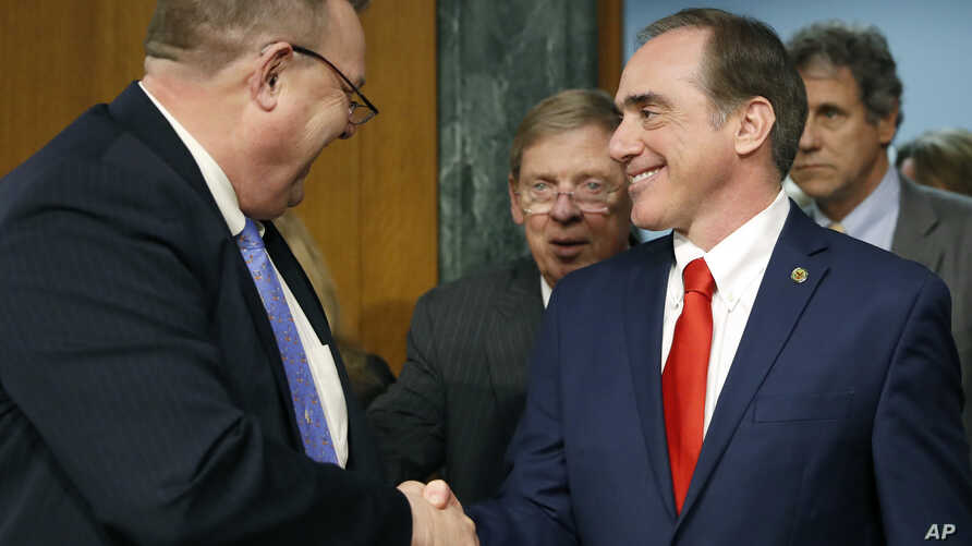 FILE - The Senate Veterans' Affairs Committee Ranking member Jon Tester, D-Mont., left, with committee chairman Sen. Johnny Isakson, R-Ga., center, shakes hands with Veterans Affairs Secretary-designate Dr. David Shulkin on Capitol Hill in Washington...