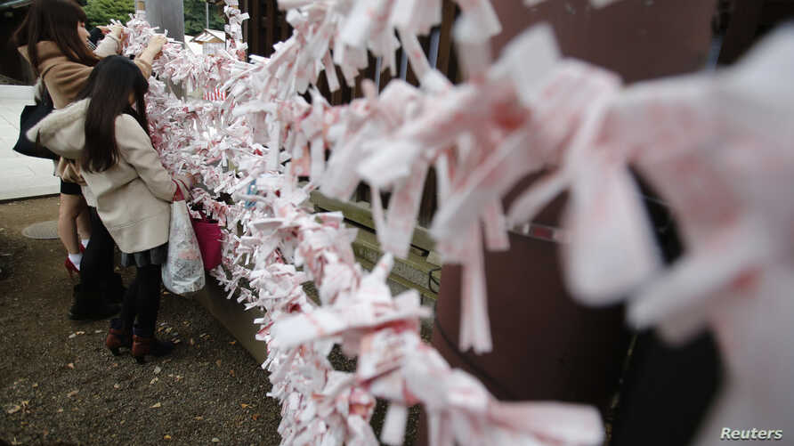 Visitors hang fortune blessing papers at Yasukuni Shrine in Tokyo, Dec. 26, 2013.