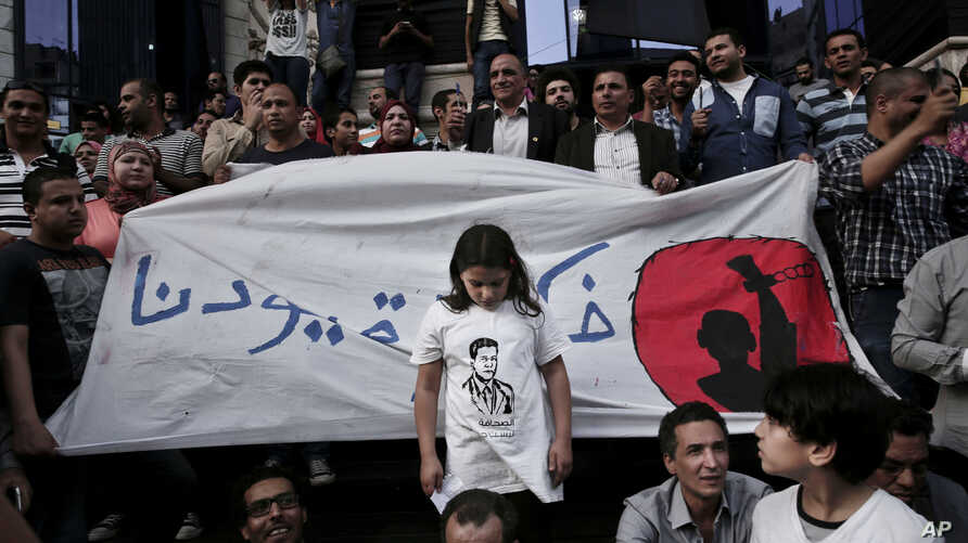 "FILE - A girl stands in front of a banner written in Arabic that reads ""remove our shackles,"" during a protest in front of the Press Syndicate in Cairo, Egypt, May 3, 2016."