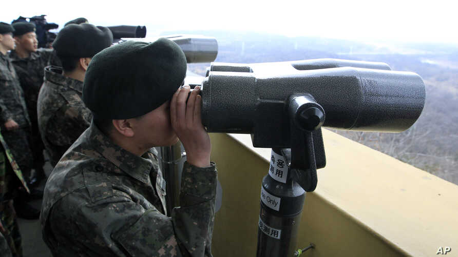 South Korean soldiers look at North Korea through binoculars from Dora Observation Post near the border village of Panmunjom, April 10, 2013.