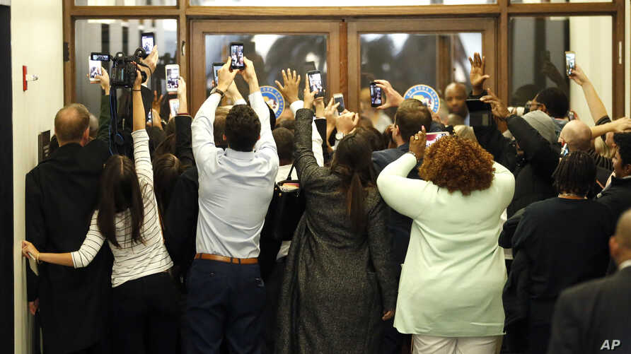 People rush the doors of the jury assembly room as former President Barack Obama departs after being dismissed from jury duty in the Daley Center, Nov. 8, 2017, in Chicago.
