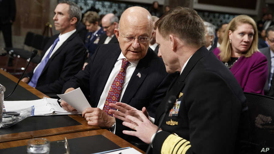 Director of National Intelligence James Clapper, center, talks with National Security Agency and Cyber Command chief Adm. Michael Rogers, on Capitol Hill in Washington, Jan. 5, 2017.