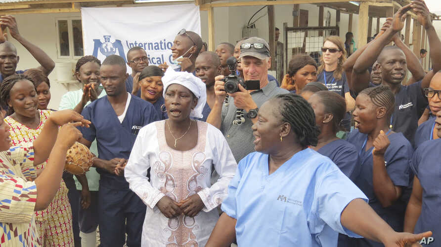 Adama Sankoh, 40, centre,  who contracted Ebola after her son died from the disease late last month stands with health officials the moment after she was discharge from Mateneh  Ebola treatment center outskirt of Freetown, Sierra Leone, Monday, Aug.