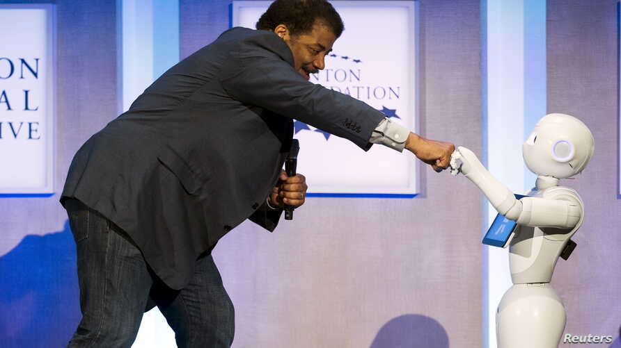Astrophysicist Neil deGrasse Tyson interacts with Pepper, a social humanoid robot developed by Aldebaran for SoftBank, during the Clinton Global Initiative's annual meeting in New York, Sept. 28, 2015.
