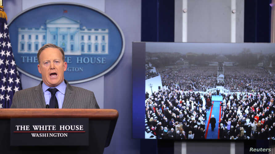 Press Secretary Sean Spicer delivers a statement while television screen show a picture of U.S. President Donald Trump's inauguration at the press briefing room of the White House in Washington, Jan. 21, 2017.