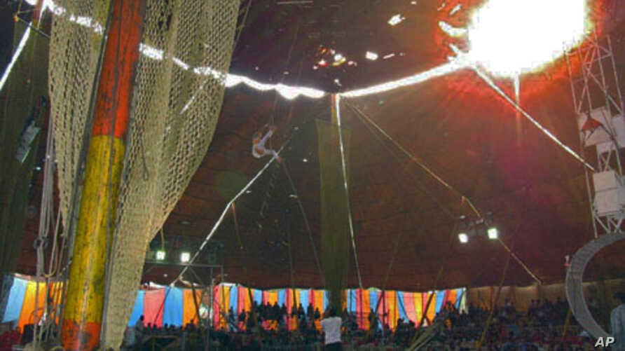A young Nepalese girl trains on the trapeze using poor safety equipment as rain leaks through the roof, in one of India's traveling circuses, in Dehradun, India, July 2011
