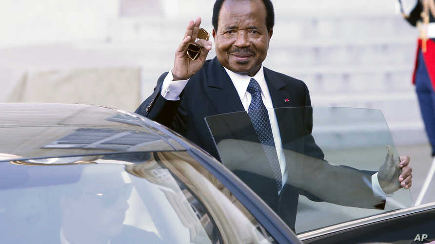 Cameroon President Paul Biya waves to reporters as he gets into his car after a meeting at the Elysee Palace, in Paris, May 17, 2014. Some of Biya's opponents accuse him of ambitions to remain president for life.