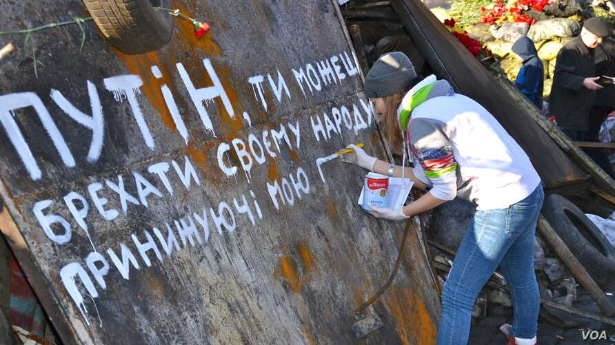 """The girl is painting a slogan that reads """"Putin you can kill us but you can't take away our freedom"""" in Kyiv's Independence Square, Ukraine, Mar. 8, 2014. (Jamie Dettmer/VOA)"""
