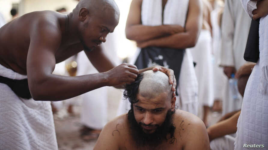 A Muslim pilgrim has his head shaved after casting pebbles at a pillar that symbolizes Satan during the annual haj pilgrimage, on the first day of Eid al-Adha in Mina, near the holy city of Mecca, Oct. 15, 2013.