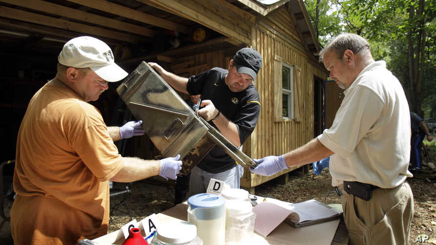 FILE - In this Sept. 2, 2010 photo, authorities in Missouri sort through evidence during a raid of a suspected meth house.