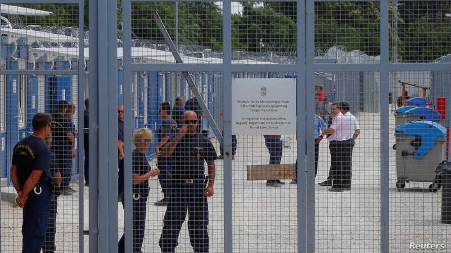 Security guards stand by the gate of the transit zone where migrants are hosted in container camps and their asylum claims are processed, in Tompa, Hungary, June 14, 2017.