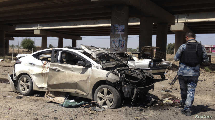 A member of the Iraqi security force inspects the site of a car bomb attack in Ramadi April 16, 2014.