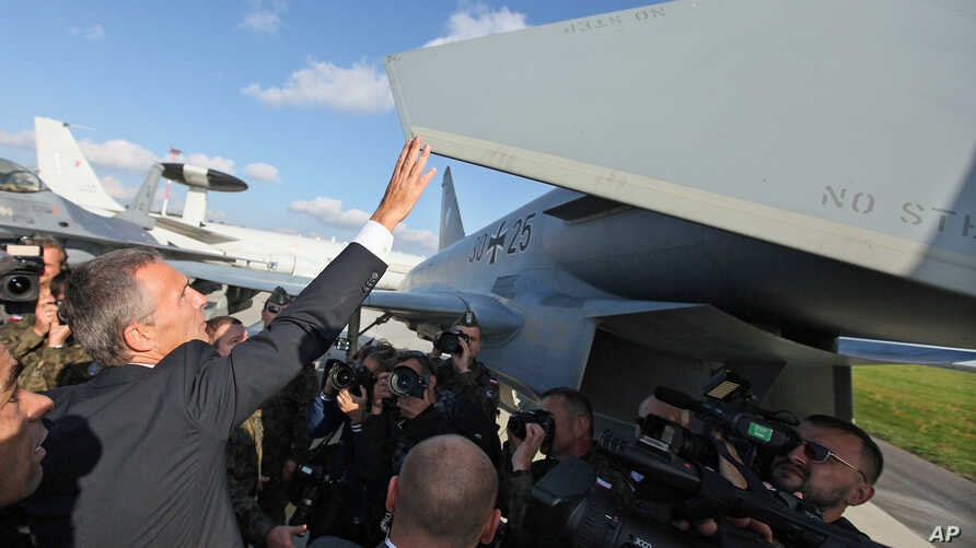 New NATO Secretary General Jens Stoltenberg of Norway touches the wing of an aircraft during his visit to the 32 Tactical Air Base in Lask, Poland, Oct 6, 2014.