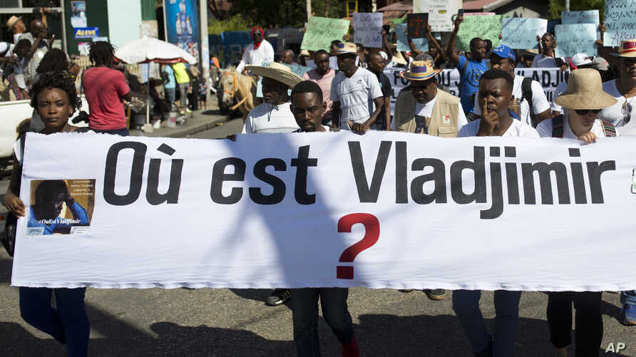 "Reporters hold a banner with a question that asks in French: ""Where is Vladjimir?"" as hundreds of journalists marched to demand an investigation into why the 30-year-old photojournalist Vladjimir Legagneur vanished while on assignment, in Port-au-Pri"