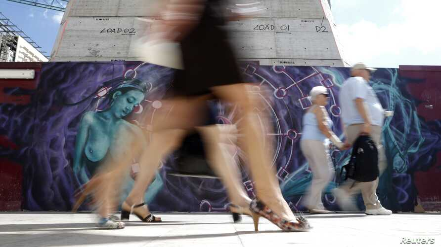 People walk past graffiti that aims to raise awareness of breast cancer ahead of Breast Cancer Awareness Month, Valletta, Malta, October 2013.
