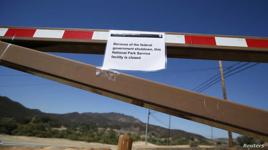A sign is seen on the gate of a National Park Service site is closed in the Santa Monica mountains, Agoura Hills, California, October 1, 2013.