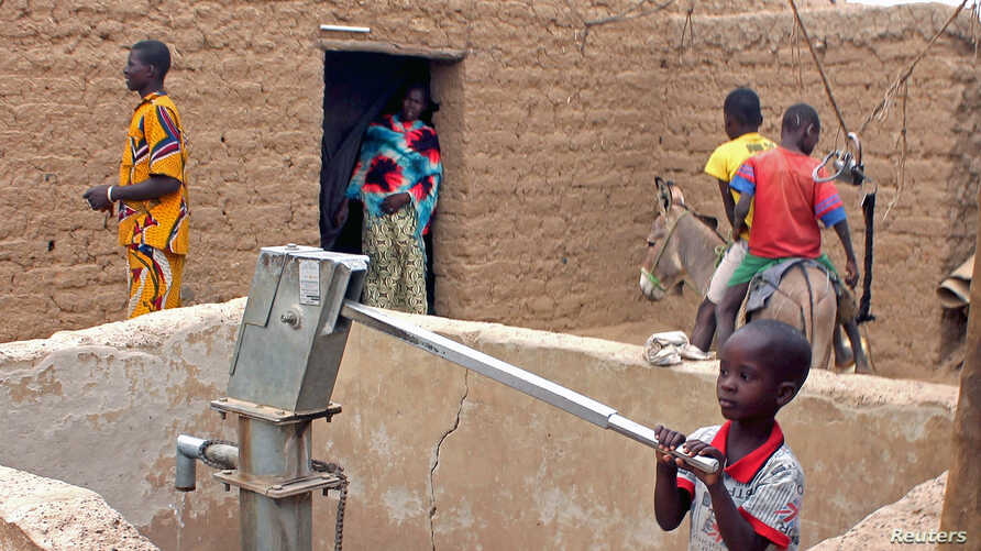 A child pumps water in the northern town of Kouroume, Mali, May 13, 2015.