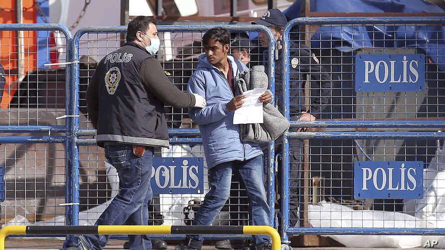 FILE-A masked Turkish police officer escorts a migrant after the first vessel transporting migrants from Greek island of Lesbos was docked in Dikili port, Turkey, putting into practice a European Union plan to stem migration to Europe, April 4, 2016....