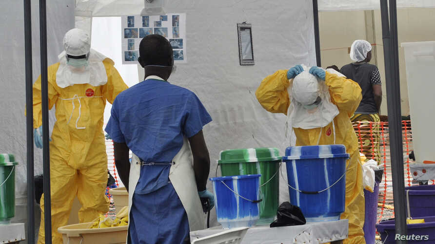 A Doctors Without Borders health worker takes off his protective gear under the surveillance of a colleague at a treatment facility for Ebola victims in Monrovia Sept. 29, 2014.