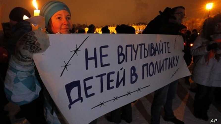 """Russian child's death follows international controversy over the Russian ban on U.S. adoptions; protest sign says """"Do not involve children in politics,"""" St. Petersburg, Dec. 26, 2012."""
