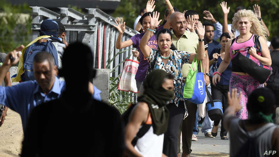 A group of pedestrians ask the activists blocking the avenue to let them cross the street during clashes between opposition demonstrators and riot police in Caracas on July 10, 2017.