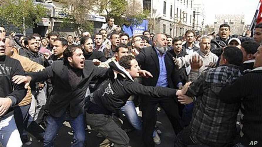 Syrians anti and pro-Assad protesters clash after Friday prayers in Damascus, March 25, 2011