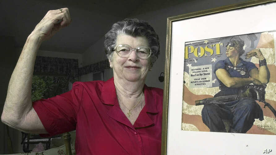 """FILE - Mary Doyle Keefe poses at her home in Nashua, N.H., with the May 29, 1943, cover of the Saturday Evening Post for which she had modeled as """"Rosie the Riveter"""" in a Norman Rockwell painting, May 22, 2002."""