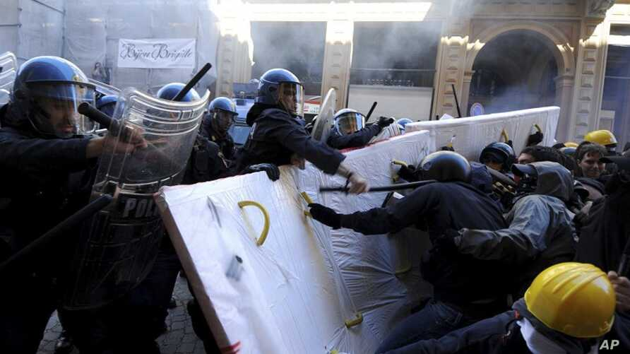 Demonstrators protesting against Italian premier Mario Monti's labor reforms, clash with police as Monti participates in a meeting in Bologna, Italy,  June 16, 2012.