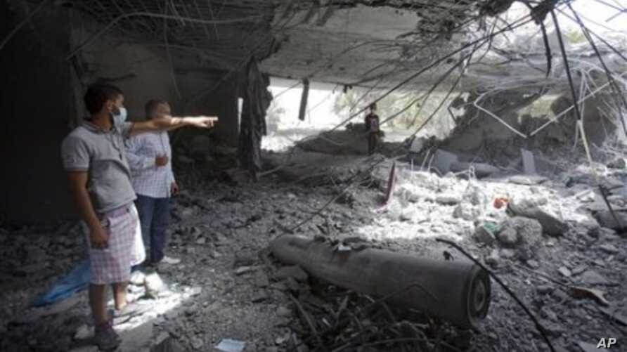 In this photo made on a government organized tour, Libyans inspect damage while standing next to an unexploded missile at the Gadhafi family compound in a residential area of Tripoli, Libya, May 1, 2011