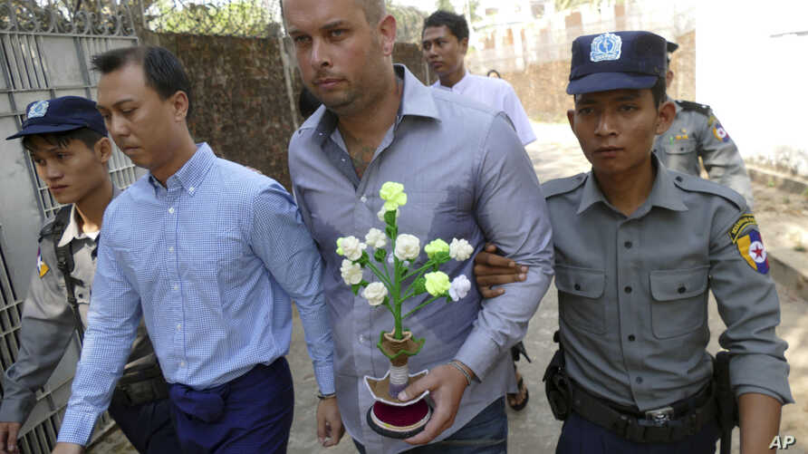 Philip Blackwood, second right, New Zealand general manager of V Gastro Bar, walks with Myanmar nationals, Bar owner Tun Thurein, second left, and its manager Htut Ko Ko Lwin, seen behind Blackwood, upon arrival for their trial at a township court Tu