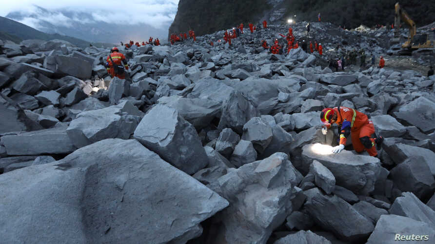 Rescue workers search for survivors at the site of a landslide that occurred in Xinmo Village, Mao County, Sichuan province, China, June 24, 2017.