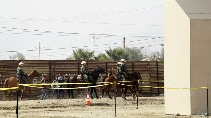 FILE - A group of people are detained by Border Patrol agents on horseback after crossing the border illegally from Tijuana, Mexico, near prototypes for a border wall, right, being constructed in San Diego, California, Oct. 19, 2017.