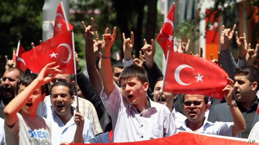 Turks hold  national flags as they march in Ankara, Turkey to protest the killings of soldiers , Wednesday, June 20, 2012, a day after Kurdish rebels attacked Turkish military units with mortars and rocket-propelled grenades in the Daglica area of Ha