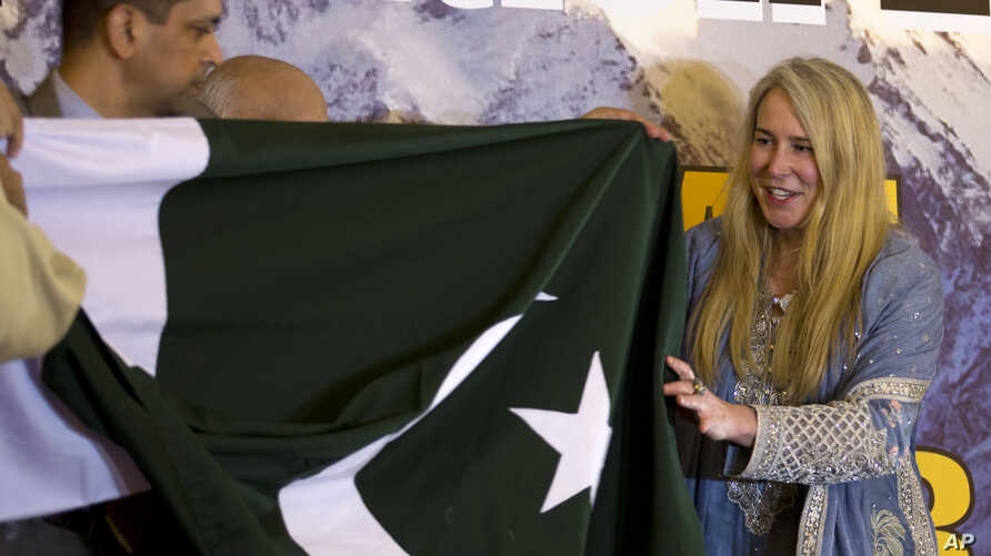 FILE - British-American mountaineer Vanessa O'Brien, right, who holds the Guinness World Record for climbing the Seven Summits in 295 days, receives Pakistani flag from officials during her news conference in Islamabad, Pakistan, June 15, 2017.