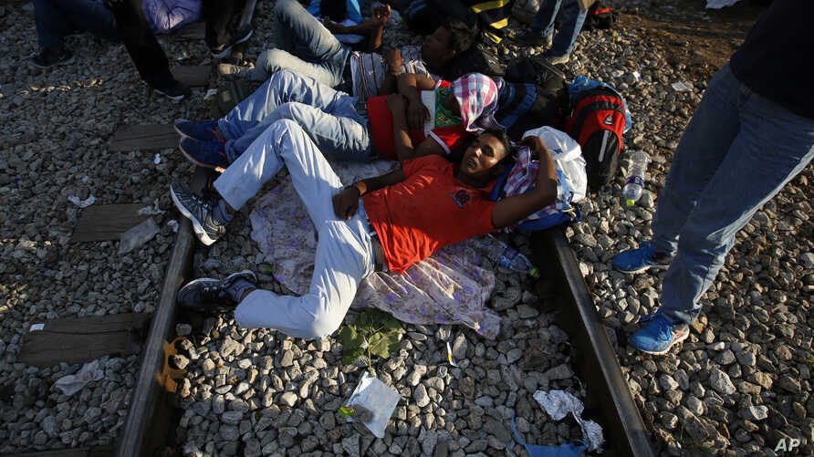 Migrants rest near the border train station of Idomeni, northern Greece, as they wait to be allowed by the Macedonian police to cross the border from Greece to Macedonia, Aug. 20, 2015.