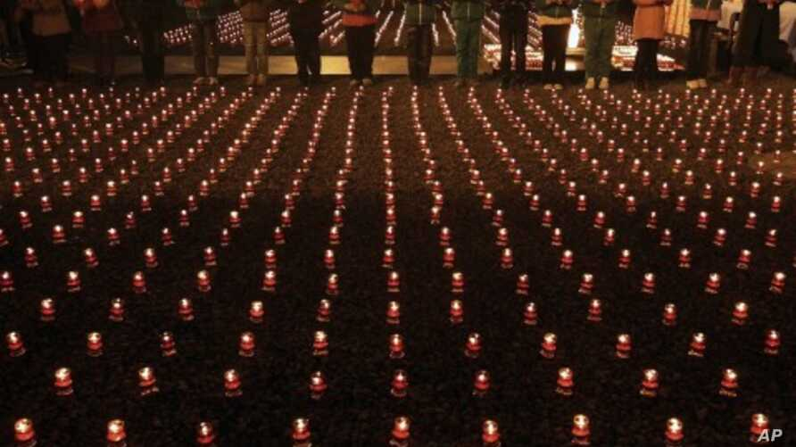 Chinese students lights candles to pray for the victims of the Nanjing Massacre near the monument to mark its 74th anniversary at the Nanjing Massacre Museum in Nanjing in east China's Jiangsu province, December 12, 2011.