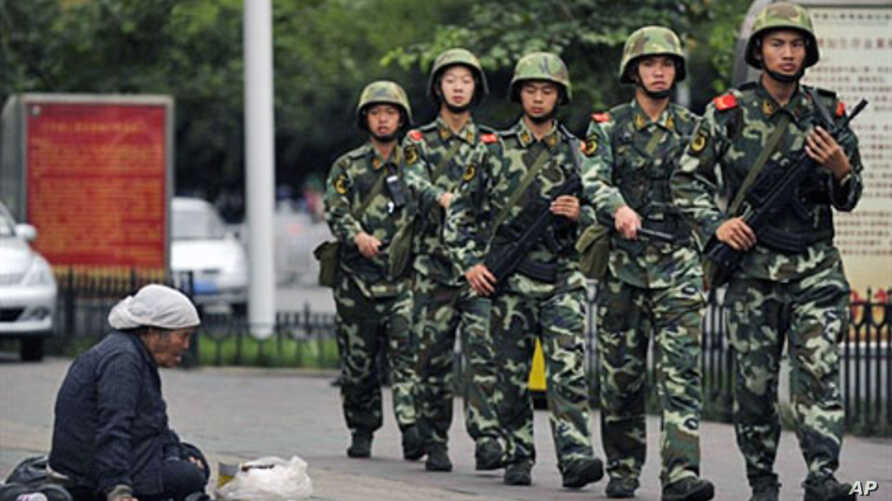 A Muslim Uighur woman begs as armed Chinese paramilitary policemen march past on a street in Urumqi on the first anniversary of deadly unrest in the western Xinjiang region,  05 Jul 2010