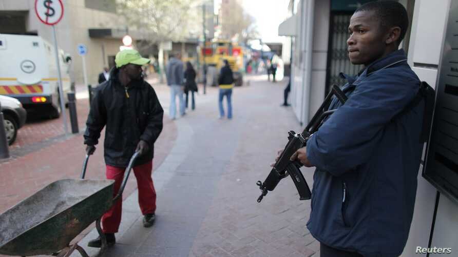 A private security guard stands outside of an ATM machine in downtown Cape Town, South Africa, June 9, 2010.