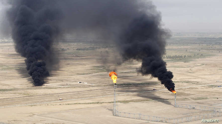 FILE - An aerial view of excess gas burning off at the al-Ahdab oil field in Wasit province, Iraq.