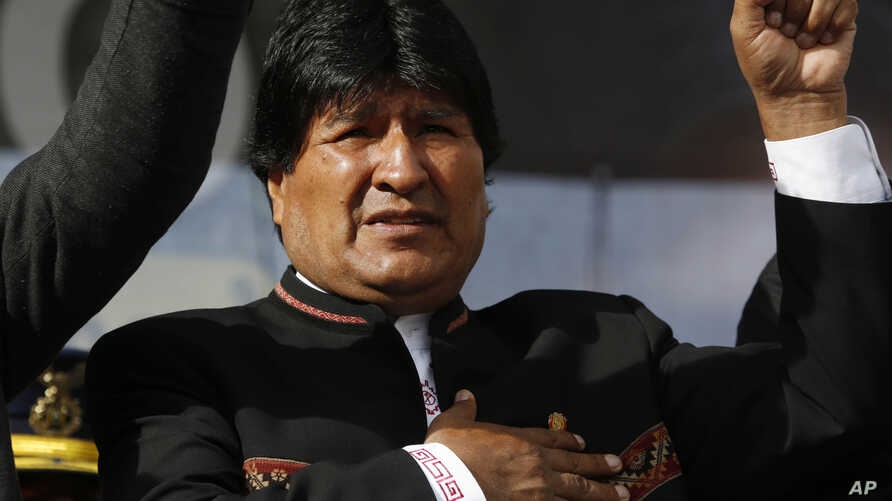 One day after a referendum on expanding presidential term limits, Bolivia's President Evo Morales sings his national anthem at a signing ceremony for the expansion of a road that connects the capital with the nearby city of El Alto, in La Paz, Bolivi